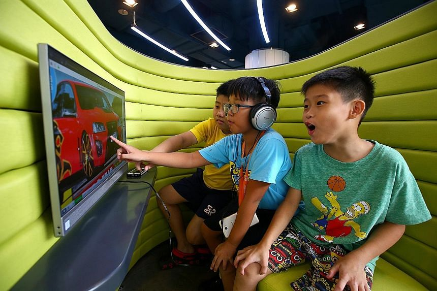 From left: Tan Xing Wei, Joseph Tan, both 11, and Tan Xing Ming, nine, trying out the touchscreen computer at Yishun Library's new Digital Learning Zone yesterday.