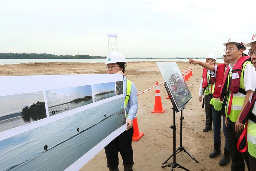 Mr Lawrence Wong (right) on a site visit at Pulau Tekong in 2016, where empoldering is being used in reclamation works. The method involves building a dike around the area to be reclaimed, then draining the water from it, creating a low-lying tract o