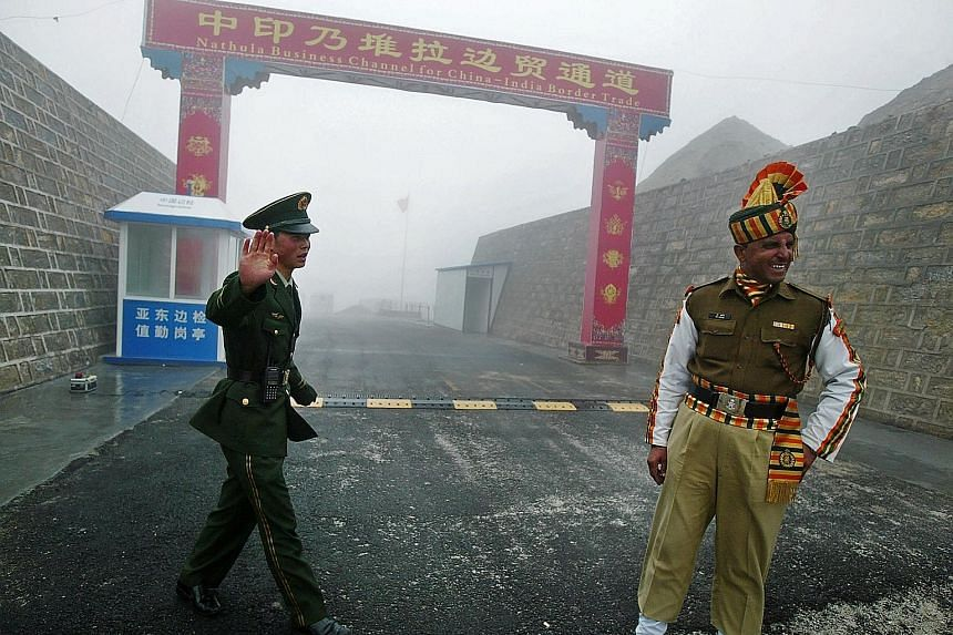 A Chinese soldier and an Indian soldier at the Nathu La border crossing between India and China. US geopolitical intelligence platform and publisher Stratfor, in an assessment of recent satellite imagery of two Chinese and two Indian airbases, said a