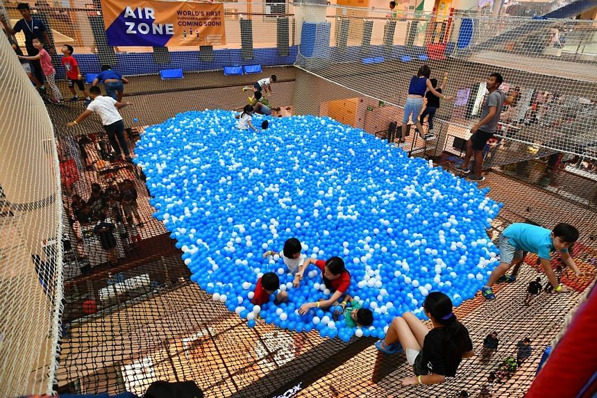 """Children under seven must be accompanied by an adult to enter the suspended ball pit at City Square Mall. Left: A ball pit """"lifeguard"""" attending to a child yesterday."""