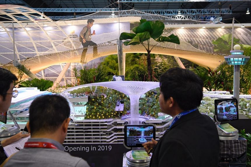 A visitor walks across a replica of the Sky Nets attraction which will be featured in the upcoming Jewel Changi Airport, at the Changi Airport booth at the Singapore Airshow.