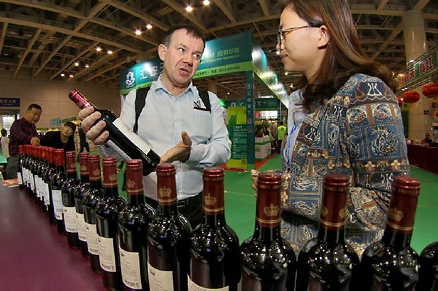 A merchant presents wines to visitors during the 10th Yantai International Wine Exposition in Yantai, East China's Shandong province.