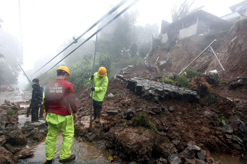 Workers clear materials from a landslide, caused by heavy rain, covering a main road in Bogor, West Java, on Feb 5, 2018.