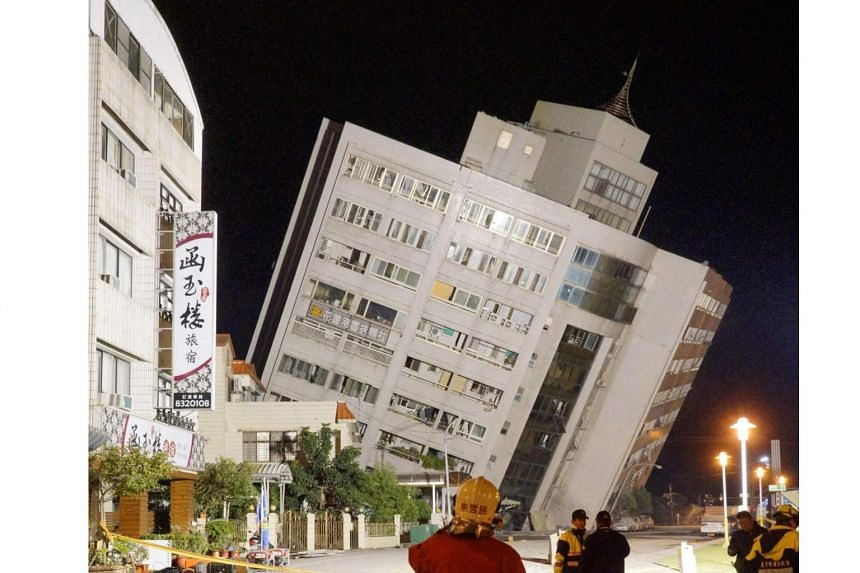 Rescue workers block off the area outside a building which tilted to one side after its foundation collapsed in Hualien after a strong 6.4-magnitude quake rocked eastern Taiwan early on Feb 7, 2018.