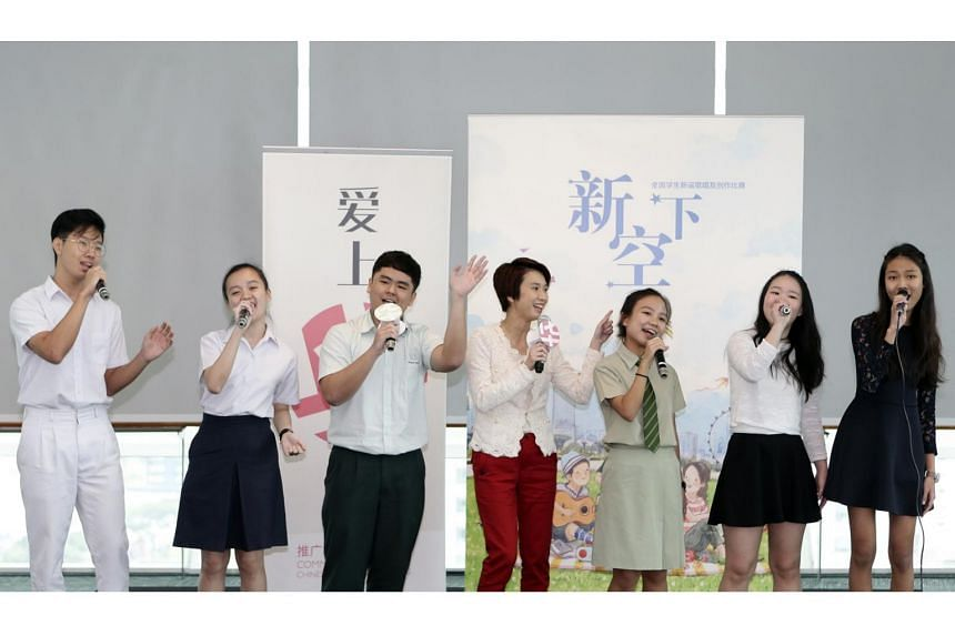 Senior Parliamentary Secretary for Education Low Yen Ling (fourth from left) performing with students at a press conference at the National Library on Feb 7, 2018.