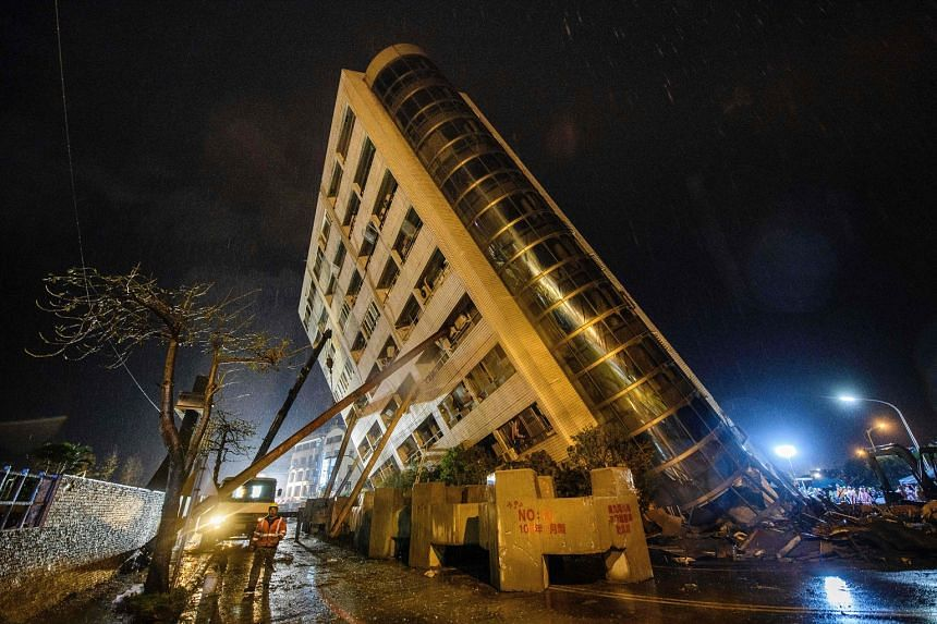 A rescue worker walks past beams used to prop up the Yun Tsui building as it leans to one side after an overnight earthquake in the Taiwanese city of Hualien on Feb 7, 2018.