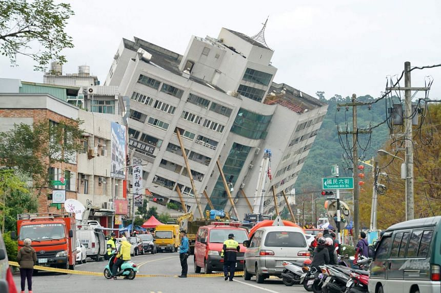 Rescue and emergency workers block off a street where a building came off its foundation, the morning after a 6.4 magnitude quake hit the eastern Taiwanese city of Hualien, on Feb 7, 2018.