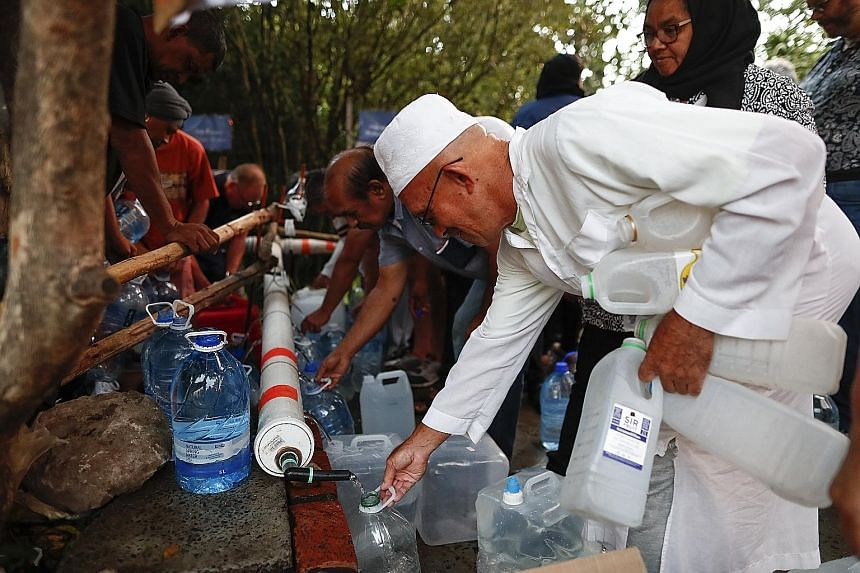 Residents of Cape Town collecting drinking water from a mountain spring collection point on Jan 31.