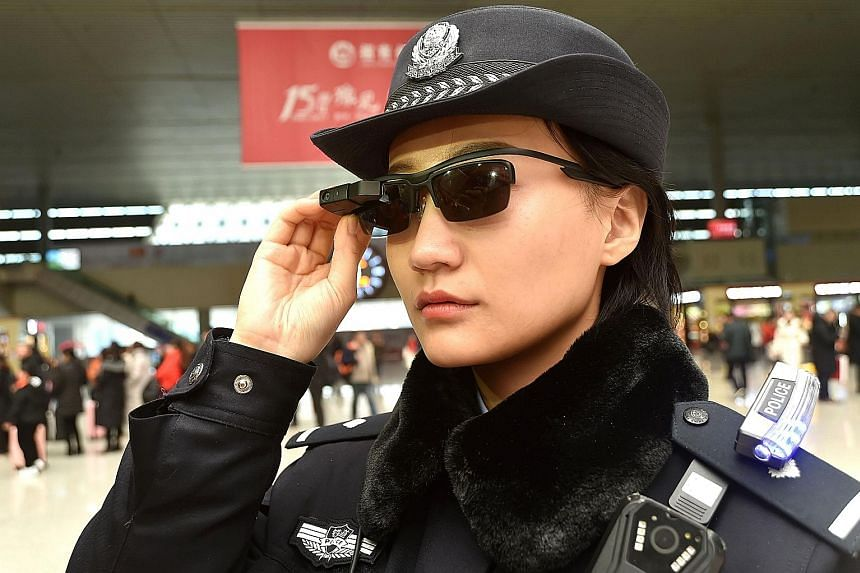 A police officer wearing a pair of smartglasses with a facial recognition system at a railway station in Zhengzhou, China's central Henan province. The high-tech sunglasses are able to spot suspects.
