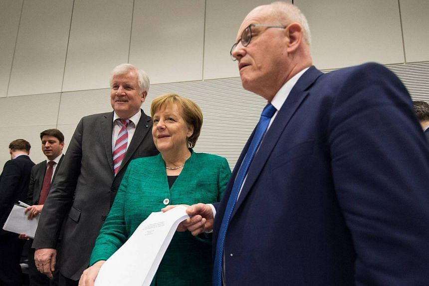 Leader of the conservative Christian Social Union party Horst Seehofer (left), German Chancellor Angela Merkel (centre) and parliamentary group leader of the conservative CDU/CSU party fraction, Volker Kauder (right) show a copy of the coalition agre