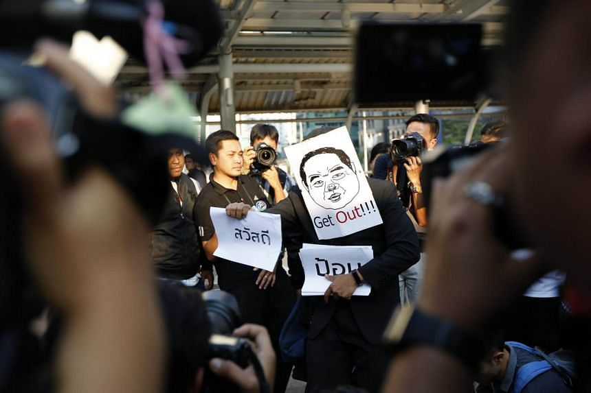 A Thai political activist wears a mask depicting Thai Deputy Prime Minister and Defense Minister General Prawit Wongsuwan with the message 'Get Out!' as he holds a symbolic protest near the Chong Non Si BTS station in Bangkok, Thailand.
