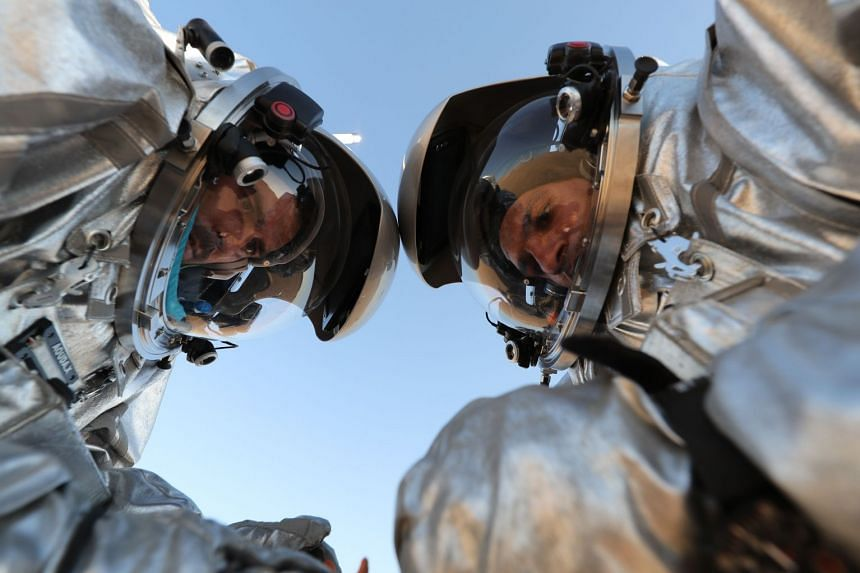 Members of the AMADEE-18 Mars simulation mission wear spacesuits while conducting scientific experiments.