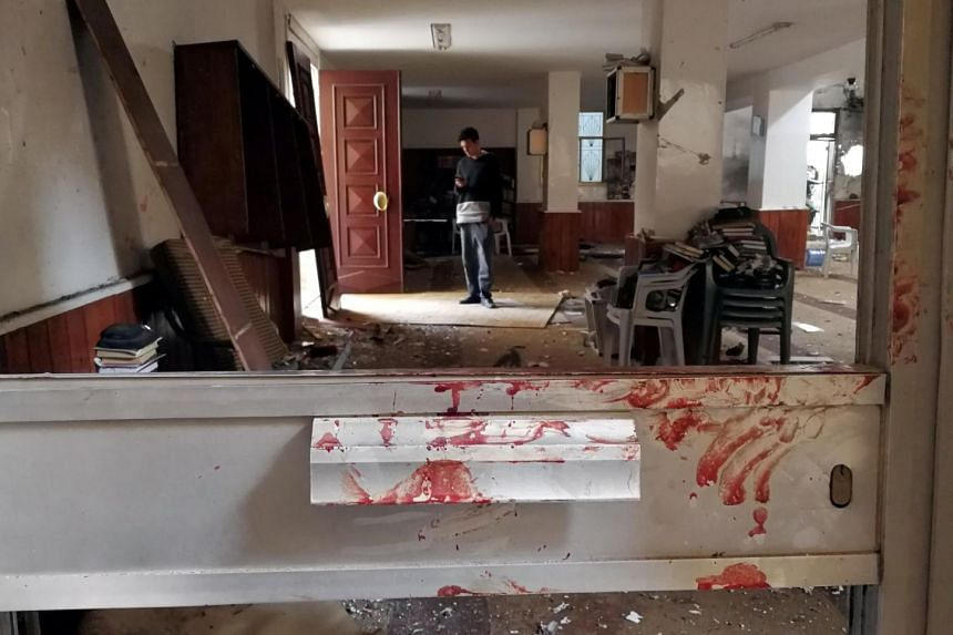 Blood stains a door following a twin bombing inside a mosque in Benghazi, Libya.