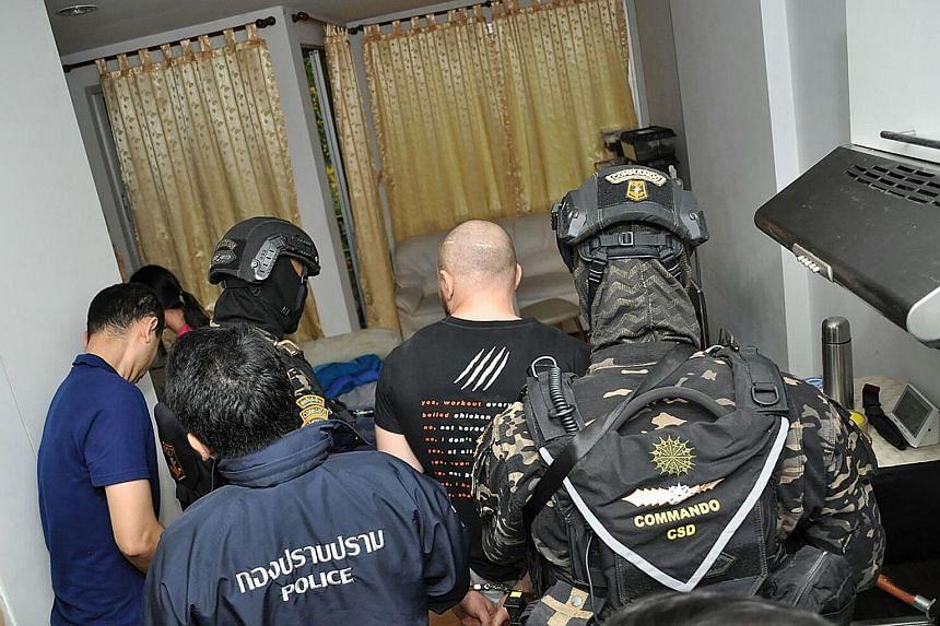 Thai police arresting Russian national Sergey Medvedev.
