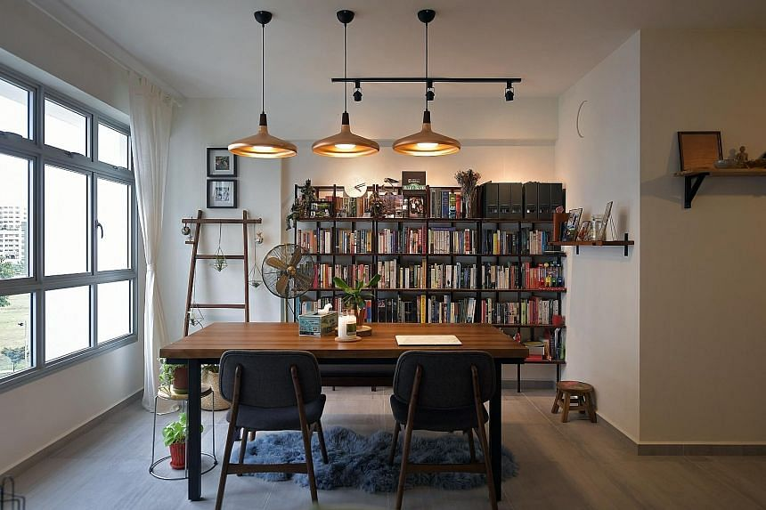 The bookshelves behind the dining table (above) in the home of Ms Joy Fang and Mr Daryll Nanayakara (both left) are among the online purchases the married couple made. They also added design elements such as a turquoise wall in the living room (below