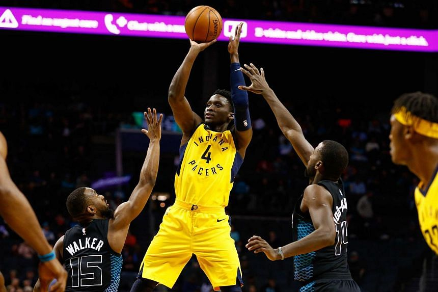 Indiana Pacers guard Victor Oladipo shoots the ball between Charlotte  Hornets guard Kemba Walker (left d9868e749
