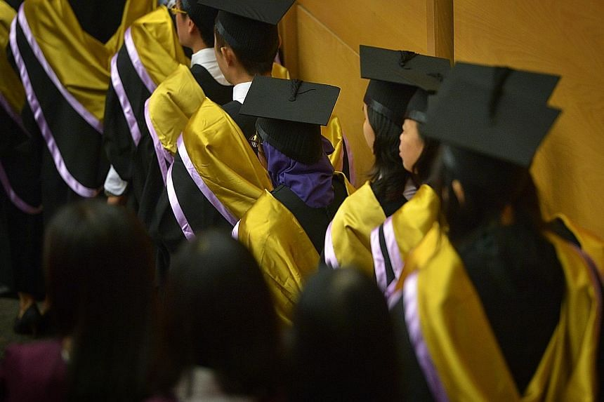 Graduating students at a Nanyang Technological University commencement ceremony. Genes may help determine how long children stay in school, but some of those genes operate at a distance - by influencing parents, researchers have found.