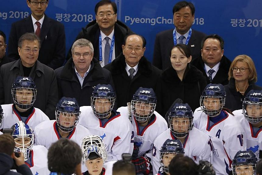 South Korean President Moon Jae In, International Olympic Committee President Thomas Bach, North Korea's ceremonial leader Kim Yong Nam and North Korean leader Kim Jong Un's sister, Kim Yo Jong, pose with Korea women's hockey players.