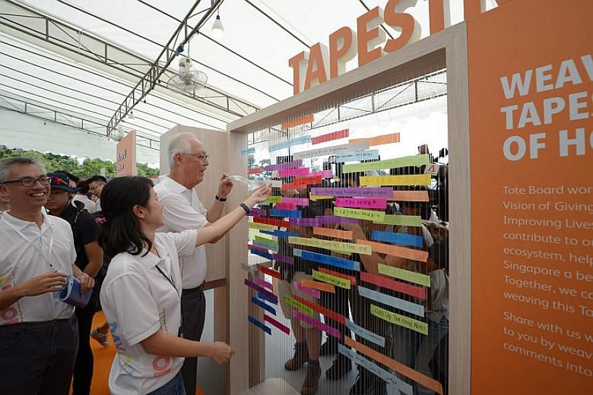 """ESM Goh Chok Tong inserts a piece of tapestry with his message """"Give Hope Spread Happiness"""" at the Tote Board Singapore's celebration of 30 years of giving at a Gardens by the Bay event, A Good Day Out, on Feb 10, 2018 ."""
