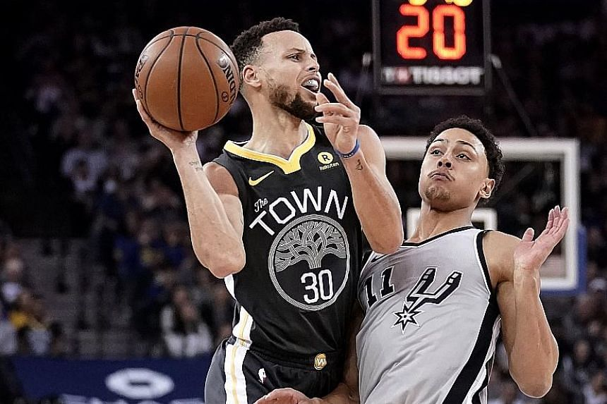 Golden State Warriors guard Stephen Curry shoots while drawing a foul by San Antonio Spurs guard Bryn Forbes in their 122-105 victory at the Oracle Arena on Saturday.