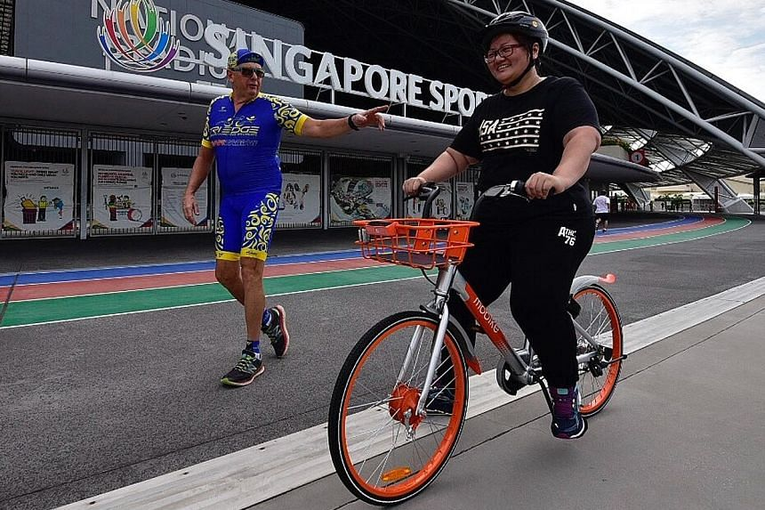 An OCBC Cycle participant cycling a Mobike while wearing a helmet under the watchful eye of OCBC Cycle's Project Training Wheels coach Michael Lyons at the Sports Hub.