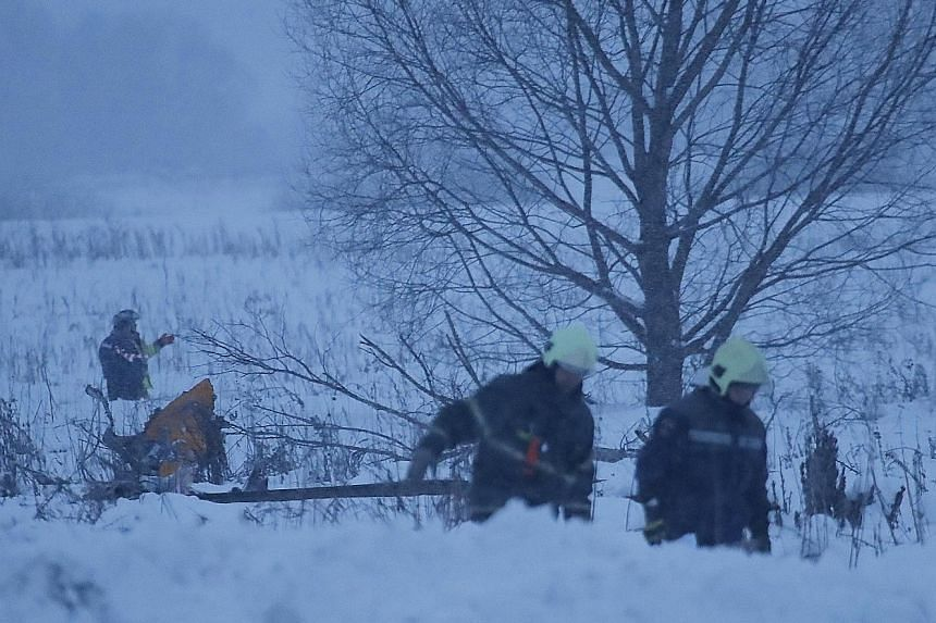 Rescue workers at the crash site near Argunovo, outside Moscow, combing through the debris yesterday. The Saratov Airlines plane was carrying 65 passengers and six crew members when it crashed shortly after take-off.