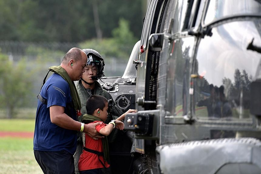 Mr Daniel Ying and his son Isaac, eight, taking a ride in a Super Puma helicopter for the first time yesterday. Their entry was selected out of more than 200 submitted for the giveaway by The Straits Times for its readers.