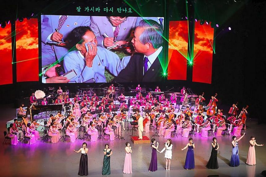 North Korea's Samjiyon Orchestra members and South Korean singer Seo Hyun (centre front) perform during a concert at a national theatre in Seoul on Feb 11, 2018.