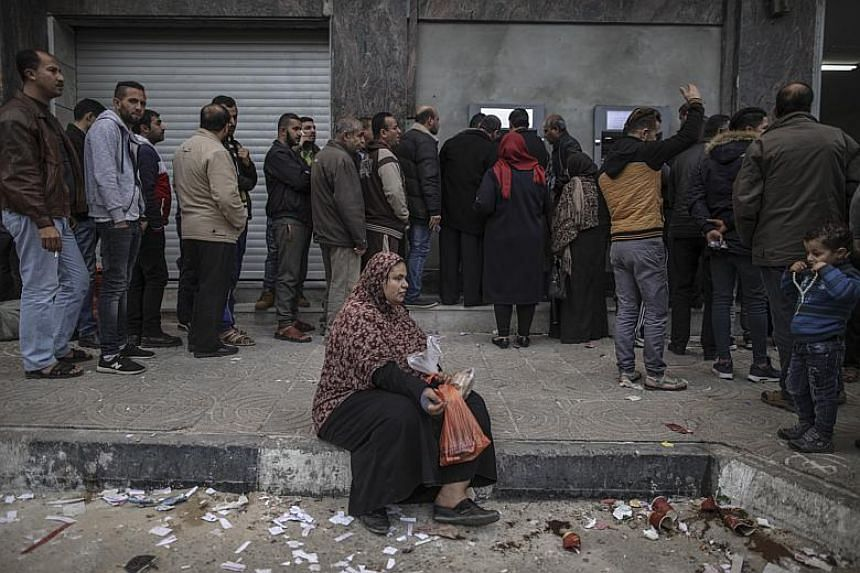 A woman begs for money as residents of Gaza line up to withdraw what money they can from ATMs at the Bank of Palestine in Gaza City, Gaza Strip.