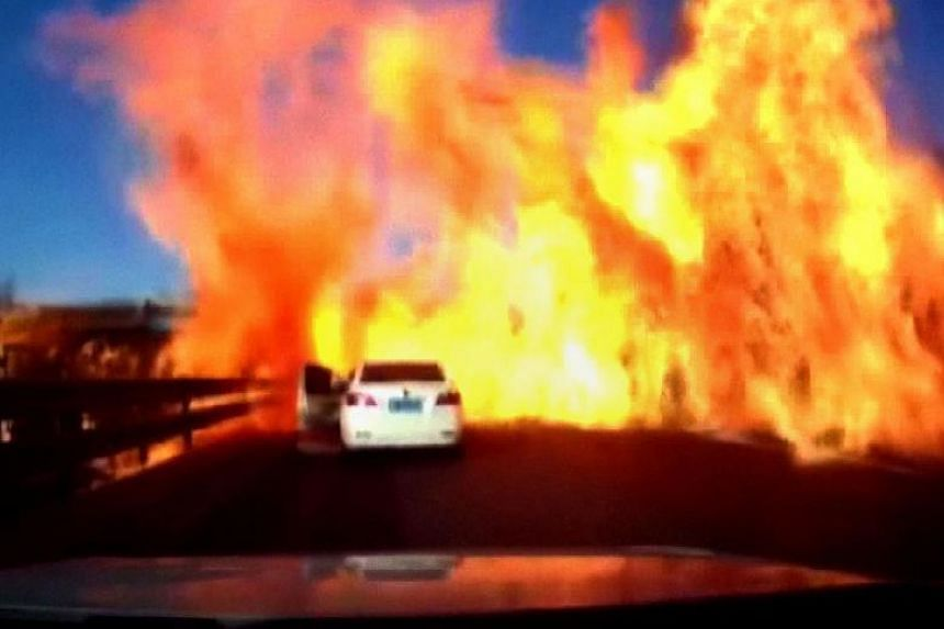 Screengrab taken from a dash cam video footage shows the door of a car (centre) opening as a wall of flames ignites a long strip of motorway along the Beijing-Harbin Expressway in Hebei province, bordering Beijing on Feb 11, 2018.