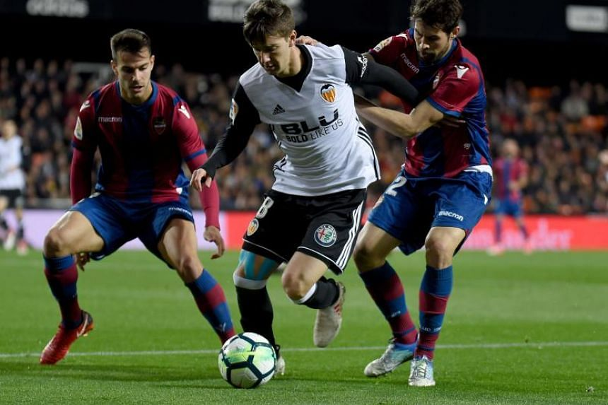 Levante's defenders Rober Suarez and Rober Pier (left) vies with Valencia's Argentinian forward Luciano Vietto during the Spanish league football match between Valencia CF and Levante UD at the Mestalla stadium in Valencia on Feb 11, 2018.