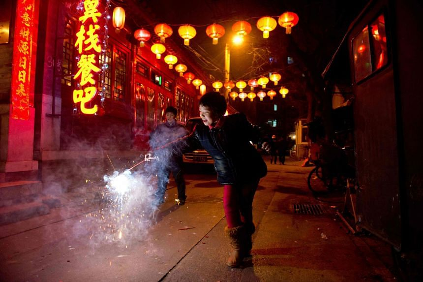 A file photo of a girl holding a firecracker in an alleyway in Beijing during the lantern festival, on Feb 24, 2013.