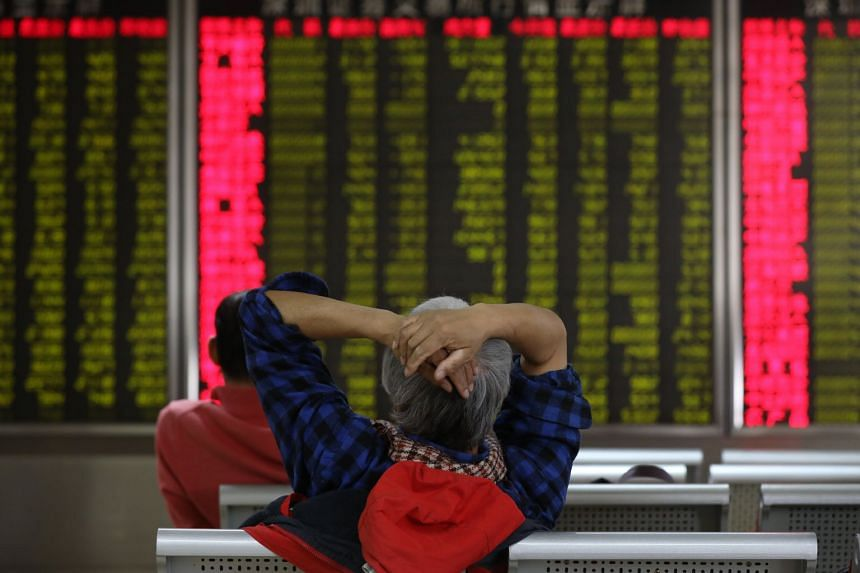A Chinese investor sits in front of an electronic board showing the stock prices at a securities brokerage house in Beijing, China, on Feb 9, 2018.