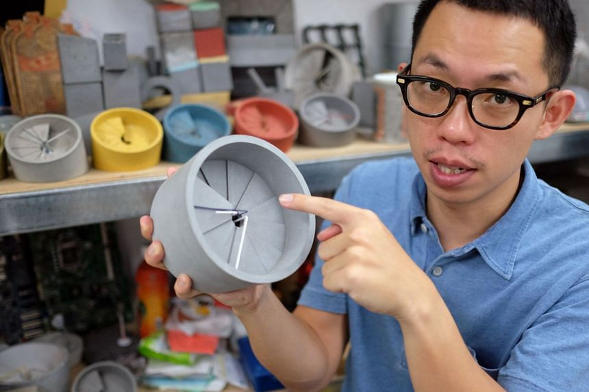 Jewellery and watchmaker Sean Yu displaying a clock with a cement surface.