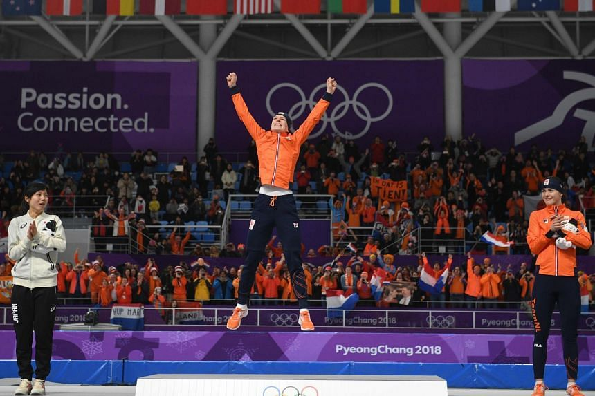 Netherlands' Ireen Wust celebrating her win on the podium with silver winner Japan's Miho Takagi and bronze winner Netherlands' Marrit Leenstra during the women's 1,500m speed skating ceremony in Gangneung on Feb 12, 2018.