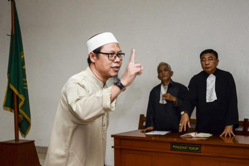 Indonesian Zainal Anshori (L) gestures in a court room prior to his trial in Jakarta on February 12, 2018. The Indonesian leader of an Islamic State-linked militant group was jailed for seven years February 12 over plans to smuggle weapons from the