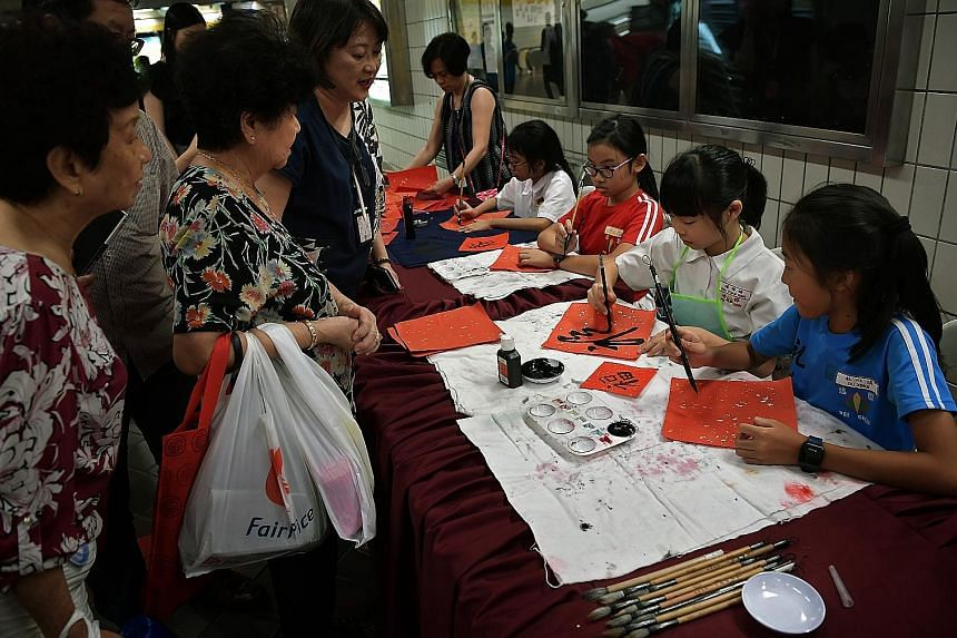 Pupils from Pei Chun Public School demonstrating the art of Chinese calligraphy at Toa Payoh MRT station yesterday as part of the Chinese New Year festivities. The pieces of artwork were then given to members of the public. The activity was organised