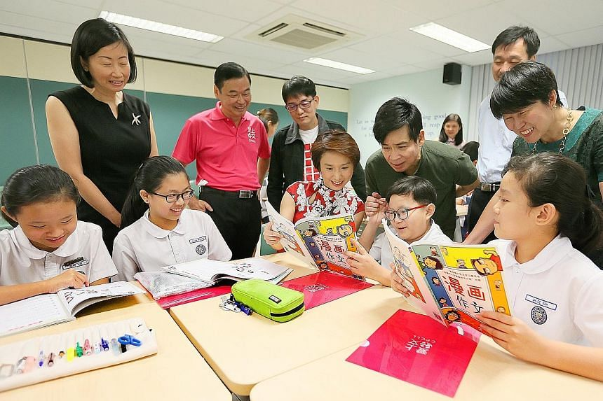 Ms Low Yen Ling (centre) with Kuo Chuan Presbyterian Primary School pupils during their essay-writing lesson yesterday. Looking on are (from left) principal Teo Ching Ling, Dr Chua Chee Lay, Mr Ang Thiam Poh, programme instructor Tan Tiaw Gem, assist