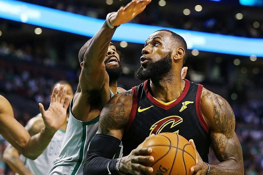 Cavaliers star LeBron James shrugging off the attention of former team-mate Kyrie Irving of the Celtics at the TD Garden on Sunday. The forward imposed his will on a day their Eastern Conference rivals paid tribute to one of their greats, Paul Pierce