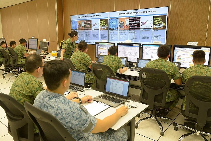 Soldiers at a demonstration showing how they would handle cyber threats at the Cyber Defence Test and Evaluation Centre in December last year. Mindef will start with 50 to 70 Cyber Specialist Awards for the first year.