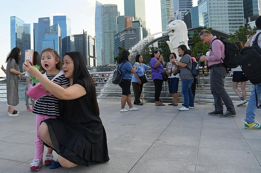 Chinese and other tourists snapping photos at the iconic Merlion Park yesterday, one of the must-visit attractions in Singapore. The surge in visitors from China last year ended Indonesia's 20-year reign as the biggest source of arrivals here.