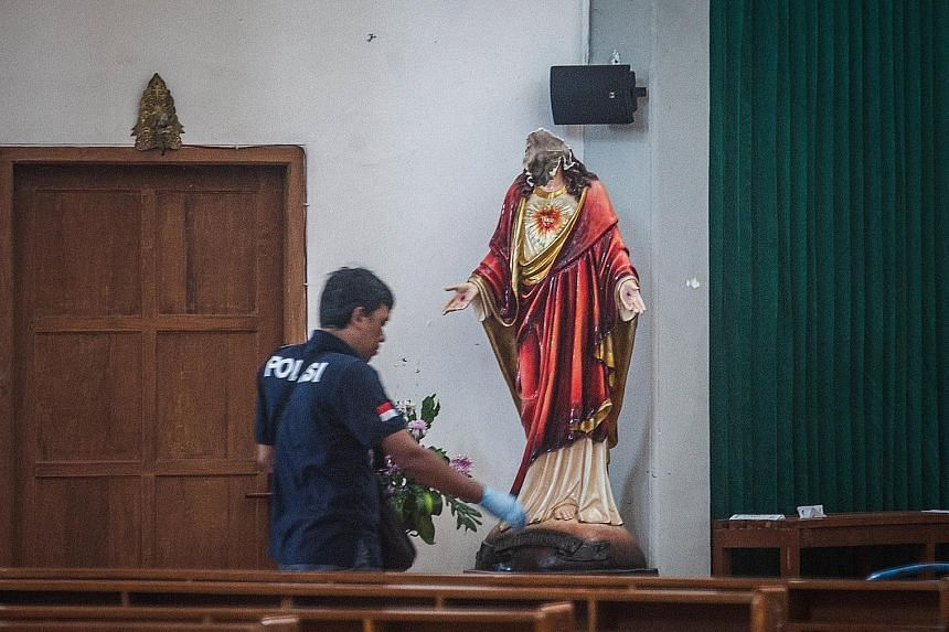 A police investigator in the Yogyakarta Catholic church where a radical Islamist had attacked people attending a service on Sunday. The man also decapitated a Virgin Mary statue with his sword.