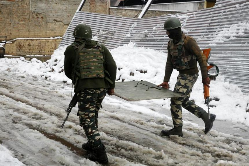 Indian paramilitary soldiers carry bullet proof shield towards an encounter site in Srinagar, the summer capital of Indian Kashmir, on Feb 12, 2018.