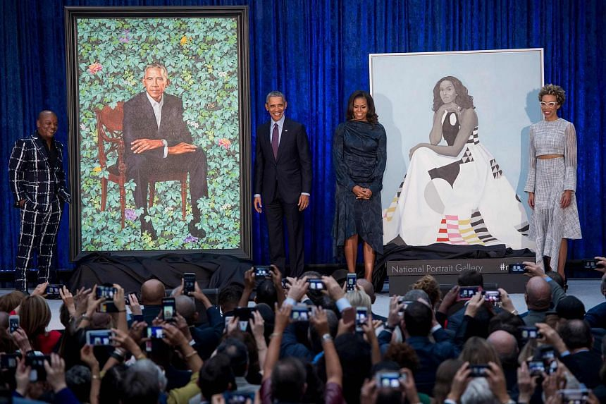 Former US President Barack Obama and former First Lady Michelle Obama stand before their portraits and artists, Kehinde Wiley (left) and Amy Sherald (right), after an unveiling on Feb 12, 2018.