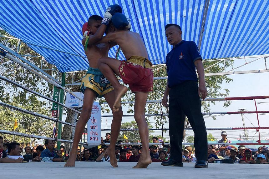 Child boxer Nanthawat Pomsod (centre), 11, fights Kritthonglek Sitkritthongkam (left) during a boxing match at a temple in Buriram province, Thailand, on Feb 2, 2018.