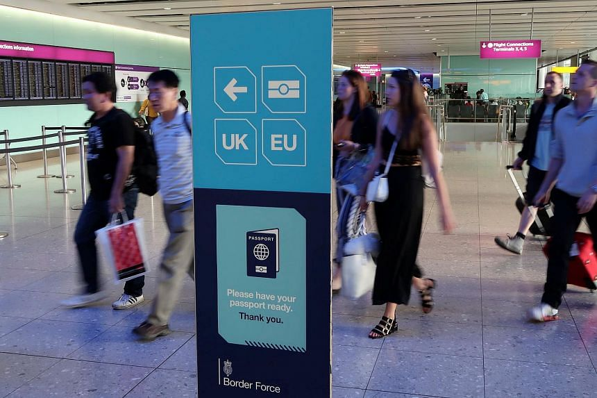 Passengers walking towards the UK border control at Terminal 2 of Heathrow Airport in London.