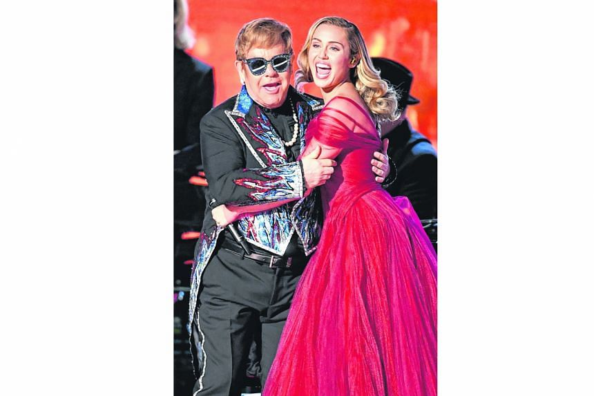 Singer Elton John (left, with singer Miley Cyrus) will not be performing residency shows in Las Vegas on May 18 and 19.