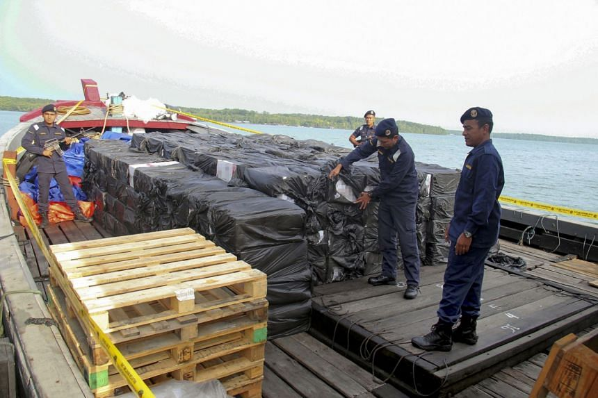 Malaysian Maritime Enforcement Agency officers yesterday showing the media some of the cigarettes that were seized from the boat on Saturday. Nine Indonesian crew members from the boat were arrested.