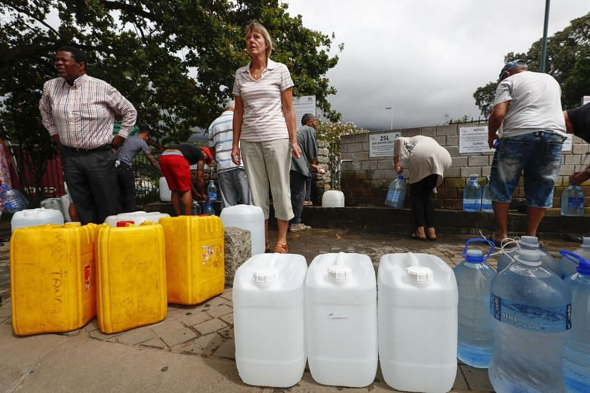 Residents of Cape Town collect drinking water from a mountain spring collection point in Cape Town, on Jan 19, 2018.