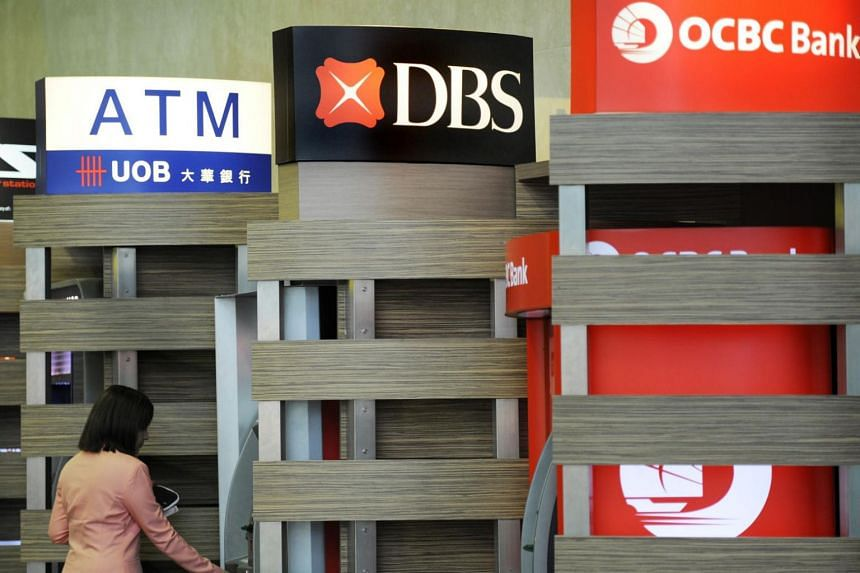 A customer standing in front of ATM machines belonging to DBS, OCBC and UOB at Changi Airport.